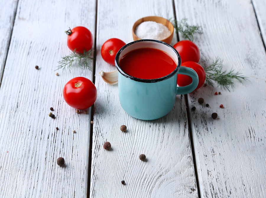 Homemade tomato juice in color mug, spices and fresh tomatoes on