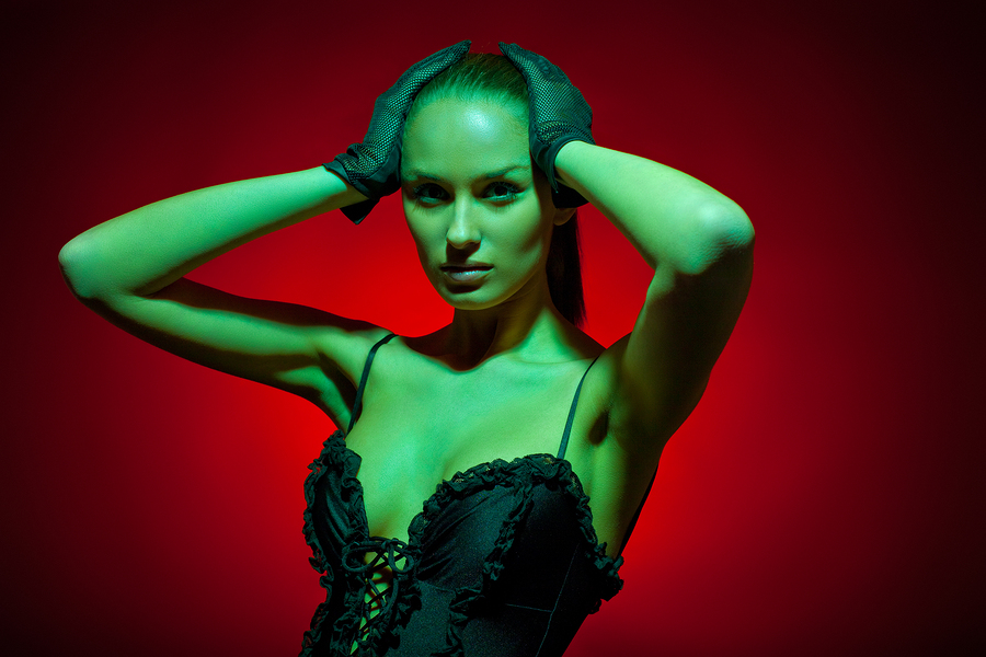 Glamorous image of fashion model in studio shot with colored gel