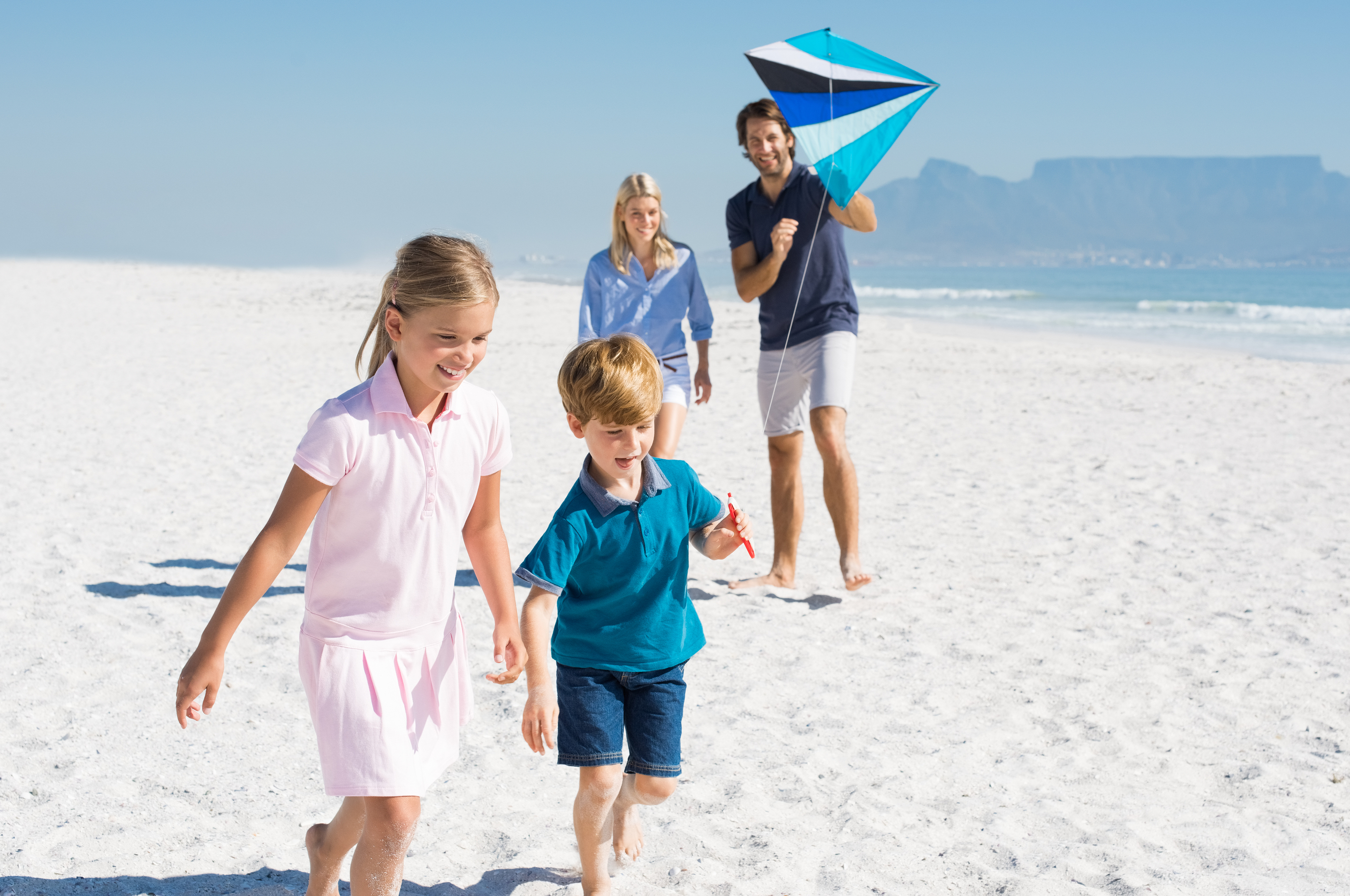Happy family running at beach with blue kite. Family playing wit