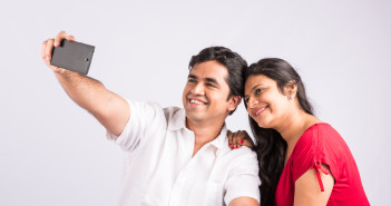 indian couple taking selfie on white background, side view, asia